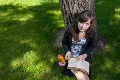 Mujeres con las flores y el libro viejo que se sientan cerca de árbol Imagen de archivo