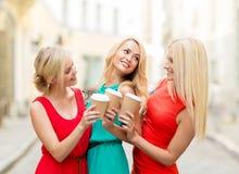 Mujeres con las tazas de café para llevar en la ciudad fotografía de archivo libre de regalías