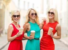 Mujeres con las tazas de café para llevar en la ciudad Imagen de archivo libre de regalías