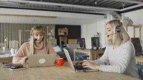 Mujeres con los auriculares con negociaciones del micrófono a clientes vía el ordenador Las mujeres con PC comunican con Skype metrajes