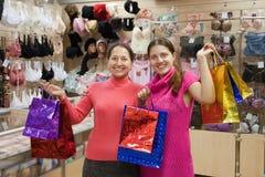 Mujeres con los bolsos de compras en departamento de la ropa interior Fotografía de archivo libre de regalías