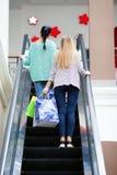 Mujeres con los bolsos en la escalera móvil Fotos de archivo