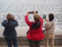 Mujeres con los dispositivos móviles Imagen de archivo
