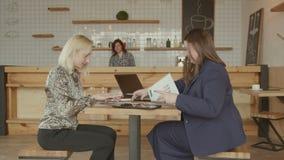 Mujeres con los documentos y artilugios que trabajan en café almacen de metraje de vídeo