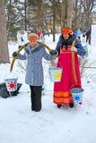 Mujeres con los ejes de balancín que llevan los cubos de agua Imagen de archivo