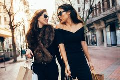 Mujeres con los panieres que caminan a lo largo de la calle de la ciudad Imagen de archivo