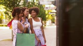 Mujeres con los panieres que miran la ventana de la tienda almacen de metraje de vídeo