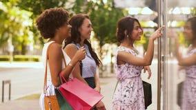 Mujeres con los panieres que miran la ventana de la tienda metrajes
