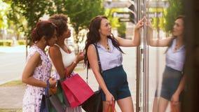 Mujeres con los panieres que miran la ventana de la tienda almacen de video