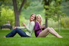 Mujeres con los teléfonos móviles en parque Fotos de archivo libres de regalías