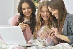 Mujeres con los teléfonos y el ordenador portátil Foto de archivo