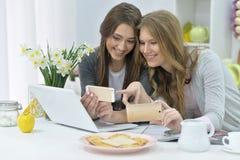 Mujeres con los teléfonos y el ordenador portátil Imagen de archivo libre de regalías