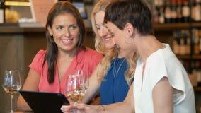 Mujeres con PC de la tableta en el vino o el restaurante de la barra almacen de video
