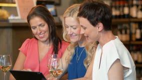 Mujeres con PC de la tableta en el vino o el restaurante de la barra metrajes