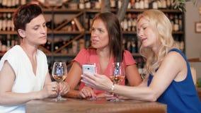 Mujeres con smartphone en el bar de vinos o el restaurante almacen de metraje de vídeo
