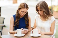 Mujeres con smartphones y café en el café al aire libre Fotografía de archivo libre de regalías