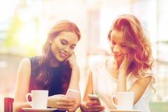 Mujeres con smartphones y café en el café al aire libre Imagenes de archivo