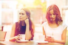 Mujeres con smartphones y café en el café al aire libre Imagen de archivo libre de regalías