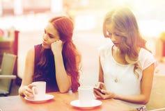 Mujeres con smartphones y café en el café al aire libre Fotos de archivo
