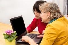 2 mujeres con un ordenador portátil Imágenes de archivo libres de regalías