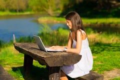 Mujeres con un ordenador portátil que se sienta en el brench Imagen de archivo libre de regalías