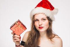 Mujeres con un regalo en el retrato rojo del Año Nuevo del casquillo aislado en blanco Foto de archivo libre de regalías