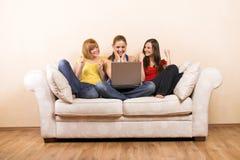Mujeres con una computadora portátil en un sofá Fotos de archivo