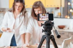 Mujeres culinarias del vlog que cuecen la afici?n en l?nea del smartphone foto de archivo