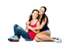 Mujeres de abarcamiento dos y de risa que se sientan jovenes Foto de archivo libre de regalías