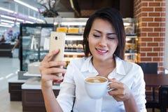 Mujeres de Asia que beben el café y miran su teléfono celular el sa Fotografía de archivo libre de regalías