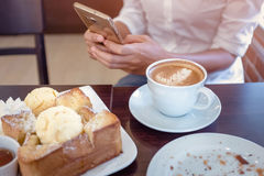 Mujeres de Asia que beben el café y miran su teléfono celular el sa Fotos de archivo