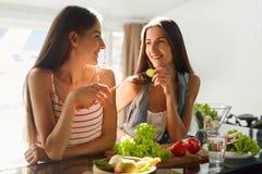 Mujeres de consumición sanas que cocinan la ensalada en cocina Comida de la dieta de la aptitud imágenes de archivo libres de regalías