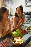 Mujeres de consumición sanas que cocinan la ensalada en cocina Comida de la dieta de la aptitud imagenes de archivo