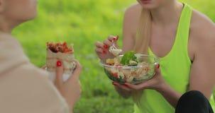 Mujeres de la aptitud que comen la ensalada fresca en un parque, comida vegetariana sana almacen de video