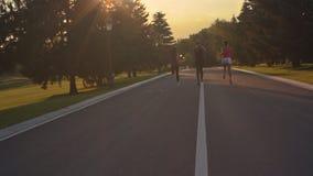 Mujeres de la aptitud que corren en el camino del parque Las mujeres agrupan el funcionamiento al aire libre en la puesta del sol metrajes