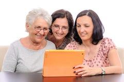 Mujeres de la familia de las memorias de la foto que usan la tableta Fotografía de archivo libre de regalías