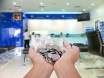 Mujeres de la mano que sostienen el dinero en el banco Imagenes de archivo