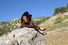 Mujeres de la remolque que se sientan en roca Foto de archivo libre de regalías