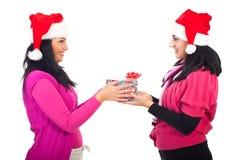Mujeres de los amigos que comparten el regalo de la Navidad Foto de archivo