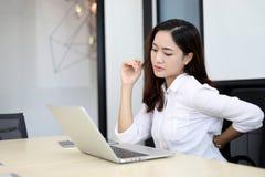 Mujeres de negocios asiáticas con pecado del dolor de espalda a la oficina y a la ha de trabajo imagen de archivo
