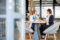 Mujeres de negocios durante un rato del café en el café fotos de archivo