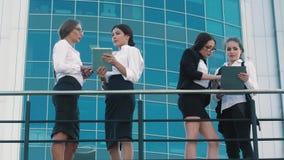 Mujeres de negocios elegantes que se colocan en terraza y que hablan el uno al otro en temas del negocio almacen de metraje de vídeo