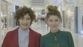 Mujeres de negocios en la alameda que registra un vídeo para sus cuentas en línea que sonríen y que envían besos a la cámara ante almacen de video