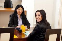 Mujeres de negocios felices en la mesa de reuniones Foto de archivo libre de regalías
