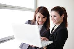 Mujeres de negocios mirada y conversación de la sonrisa imagenes de archivo