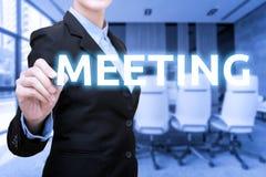 Mujeres de negocios que escriben palabra de la reunión con la sala de reunión de la falta de definición foto de archivo libre de regalías