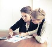 Mujeres de negocios que señalan en los diagramas Imagen de archivo libre de regalías