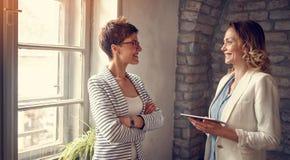 Mujeres de negocios sonrientes que intercambian ideas imagenes de archivo