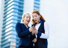 Mujeres de negocios sorprendidas que miran el teléfono elegante, recibiendo el unexp foto de archivo