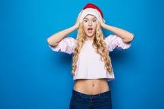 Mujeres de Santa con los bolsos La belleza Girl modelo en Santa Hat chocó aislado en fondo azul imagen de archivo